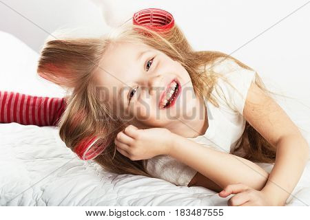 Beautiful Young Fashion Girl With Hair Curlers Are Sitting On Bed At Home