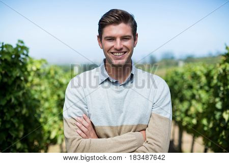 Portrait of smiling young man with arms crossed standing at vineyard against blue sky