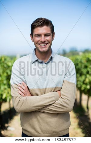 Portrait of smiling man with arms crossed standing at vineyard against blue sky