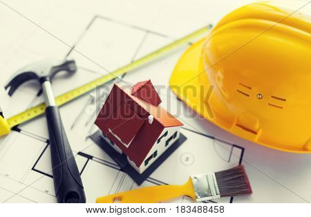 architecture, building, construction, real estate and home concept - close up of living house model on blueprint with repair tools