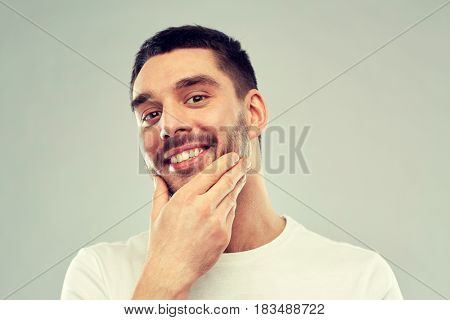 beauty, skin care, grooming and people concept - happy young man touching his face or beard over gray background