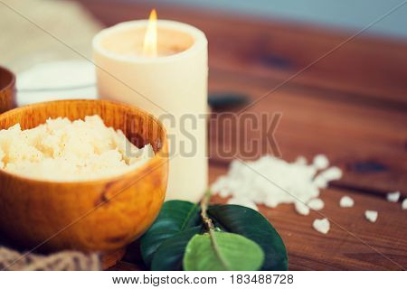 beauty, spa, therapy, natural cosmetics and wellness concept - close up of body scrub and candle on wood