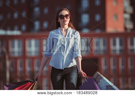 The girl walking with shopping bags on city streets at sunny day