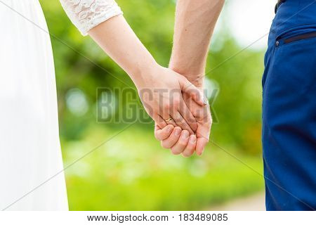 Newlyweds. Close up of loving couple holding hands in the park