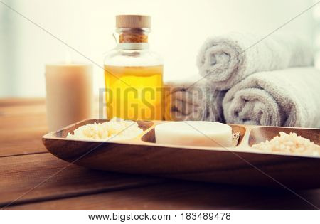 beauty, spa, body care, natural cosmetics and bath concept - close up of soap with himalayan salt and scrub in wooden bowl on table