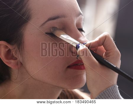 beautiful young brunette woman applying powder with a brush