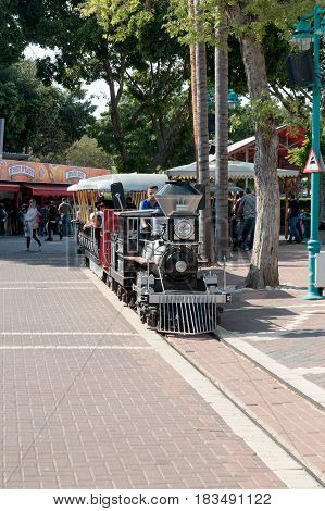 Tel Aviv Israel April 16 2016 : Visitors go by reduced copy of the locomotive drives around the amusement park run by a young man in Tel Aviv Israel