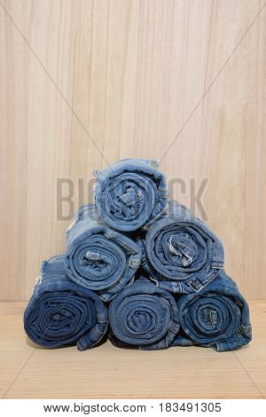 stack of rolled of jeans-wooden background