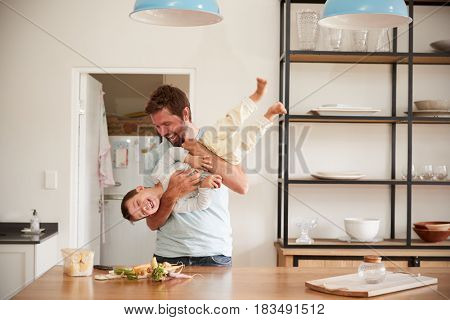 Father Playing With Son As They Prepare Food In Kitchen