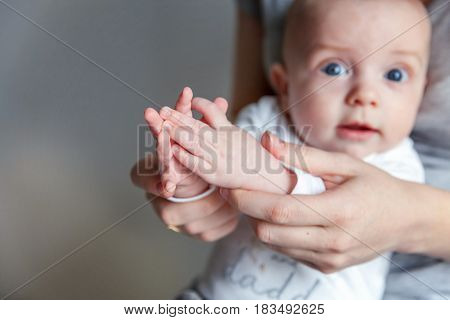 Playful cutie. Mother holding her newborn child. Family at home. Mom plays with her child