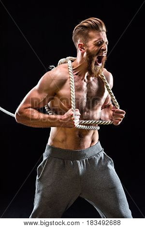 Handsome Bearded Sportsman Yelling And Pulling Rope Isolated On Black