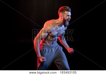 Handsome Bodybuilder Gesturing And Yelling Isolated On Black With Dramatic Lighting