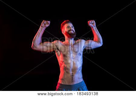 Happy Bodybuilder Celebrating Triumph Isolated On Black With Dramatic Lighting