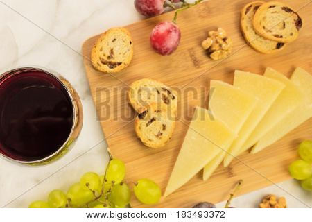 A closeup of a glass of red white wine at a tasting, with grapes, cheese, and a place for text. Selective focus