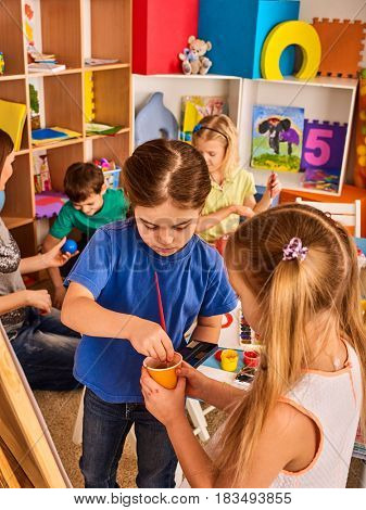 Small students with teacher painting in art school class. Two little girl children drawing by paints on easel. Craft drawing education develops creative abilities. Collective creativity in kids club.