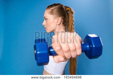 Young Sportswoman Training With Dumbbell Isolated On Blue In Studio