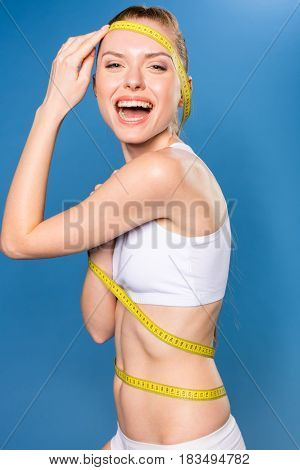 Young Sportswoman In White Underwear With Measuring Tape Isolated On Blue In Studio