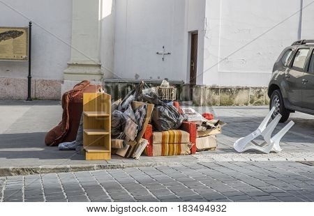 Bulky waste on the street. Broken beds, chairs, garbage furniture on pavement ready for bulky waste collection. Symbol of moving, garbage, throw-away society.