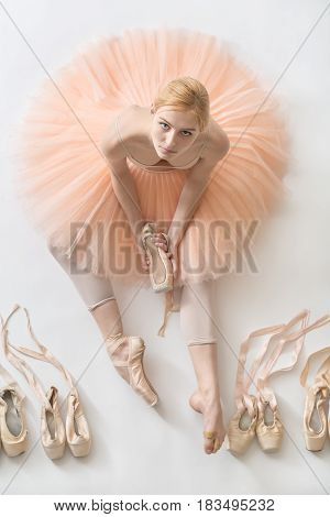 Delightful ballerina sits on the white floor and holds a beige pointe shoe in the studio. She wears a light dance wear and a peach tutu. On the sides there are ballet shoes. Top view photo.