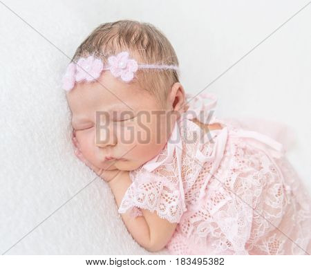 Cute princess baby napping in a laced pink suit wearing lovely hairband