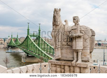 Budapest, Hungary - March 12, 2017: King Saint Stephen and horse statue located on Gellert Hill against the Liberty Bridge over Danube river. Szent Istvan Kiraly monument