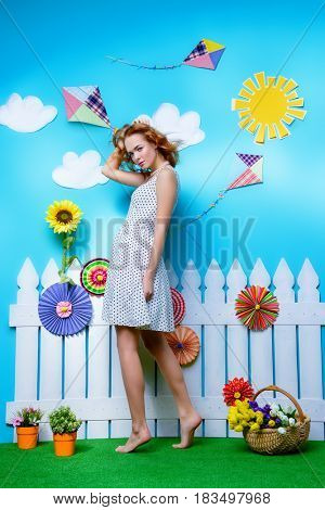 Pretty young woman with beautiful foxy hair in a summer garden decoration. Spring and summer holidays. Women's Day. Beauty, fashion concept.
