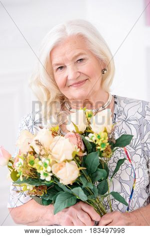 Beautiful senior woman at home with a bouquet of flowers. Happy Mother's Day. Beauty, fashion. Happy retirement.