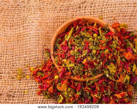 Red seasoning with pepper in a wooden cup and sacking