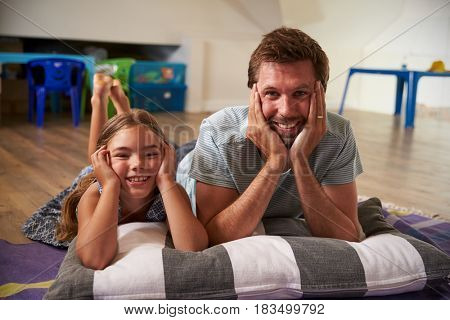 Father And Daughter Watching Television In Playroom Together