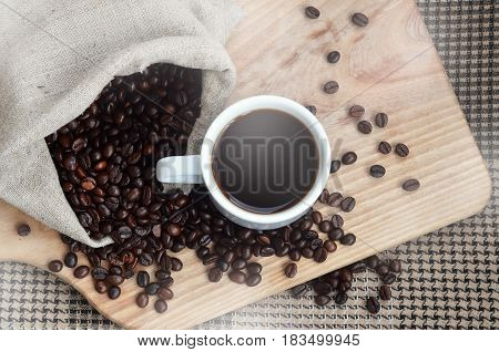 A Full Bag Of Brown Coffee Beans And A White Cup Of Hot Coffee Lies On A Wooden Surface