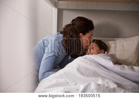 Mother Kissing Goodnight To Daughter At Bedtime
