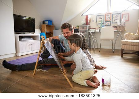 Father And Children Drawing On Chalkboard In Playroom
