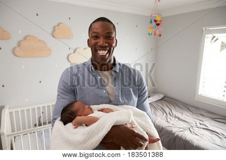 Portrait Of Father Holding Newborn Baby Son In Nursery