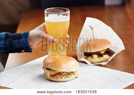 Two delicious well done burger topped with onions, tomatoes, cheddar cheese slice and lettuce with nacho chips on cutting board and glass of beer in background.