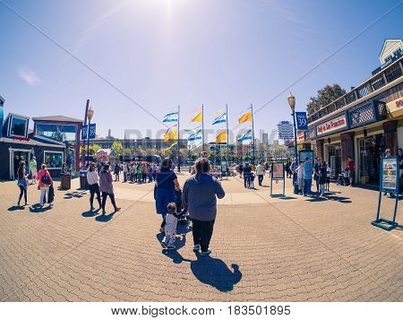 San Francisco, CA, USA - April 3, 2017: Touring family with child walking  near the entrance of Pier 39, Fisherman's Wharf