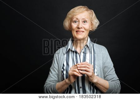 Waiting for positive news. Delighted charming retired woman expressing amazement and smiling while standing isolated in black background