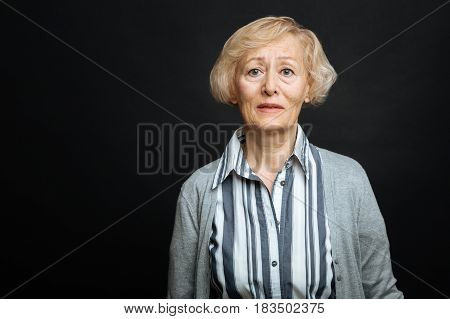 Reacting on terrible news. Upset puzzled aging woman expressing disappointment while standing isolated in black background