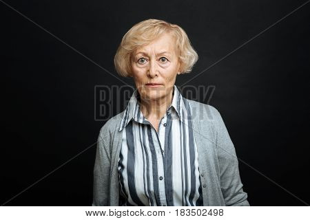 Ready to stick up for myself . Angry concentrated senior woman expressing negative emotions while standing isolated in black background