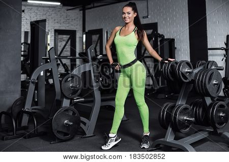 Training in the gym. Fitness girl posing and showing her figure. Fitness coach rests on the simulator after training. Sport model posing in a sports suit