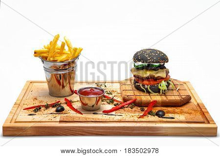 Black cheeseburger with French fries in a bucket ketchup on a wooden board