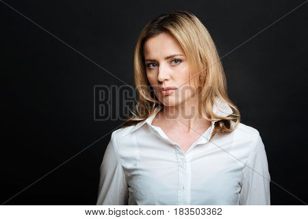 Full of confidence. Determined involved attractive woman expressing resoluteness while showing confidence and standing in black colored studio