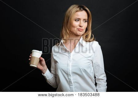 Enjoying weekend . Charismatic young optimistic woman expressing optimism while holding cup of coffee and standing in black colored studio