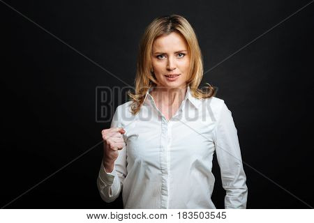 Going to prove the truth. Determined charismatic involved woman expressing determination while showing the fist and standing isolated in white background