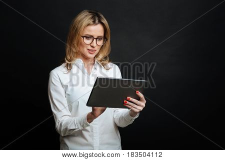 Interested in technology innovations. Concentrated smart attractive woman expressing delight and using tablet while standing isolated in black background