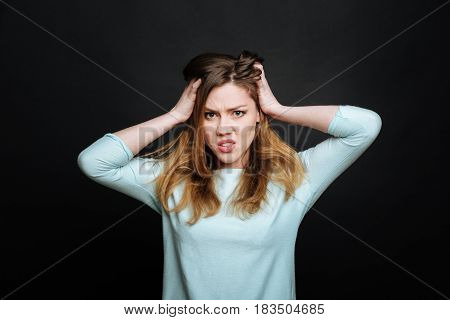 Feeling undisguised aversion. Annoyed emotional young woman expressing fury and touching her head while gesticulating wildly and standing isolated in black background