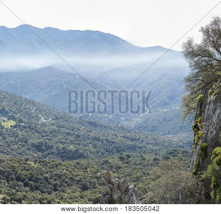 Landscape of mountains in mist and alpinist climbing rock
