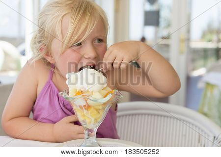 Little Kid Eating A Spoonful Of Fruit Sundae