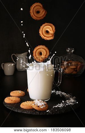 Falling Cookies To Glass Of Milk With Splash On Black Background