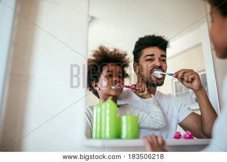 Portrait of an african american father and daughter brushing teeth in the bathroom.