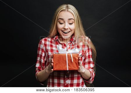 Overwhelmed with happy emotions. Cheerful happy sincere girl expressing delight and receiving gift box while standing against black background